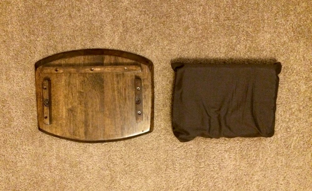 The pillow is in the foam next to the wooden lap desk.