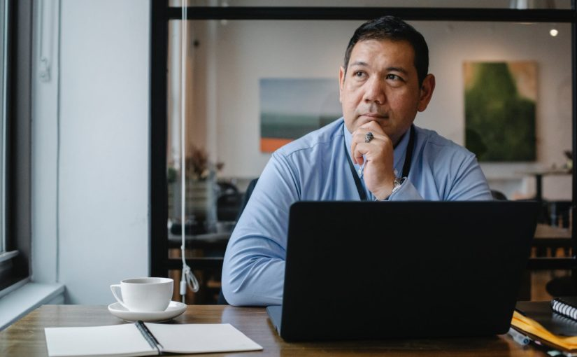 thoughtful ethnic businessman using laptop while working in office